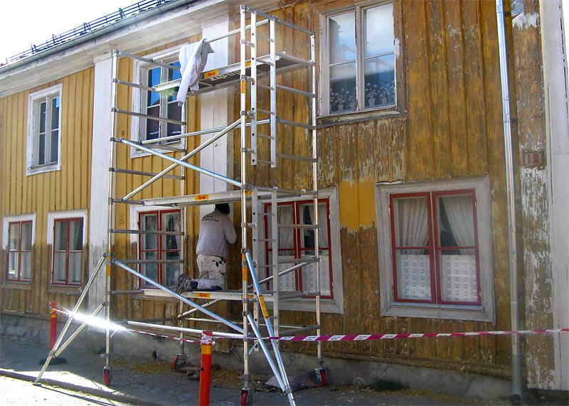Målare målar om ett slitet gult hus från en byggställning